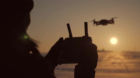 manipulacja : Girl operating a drone with remote control. Silhouette woman drone pilotage at sunset.