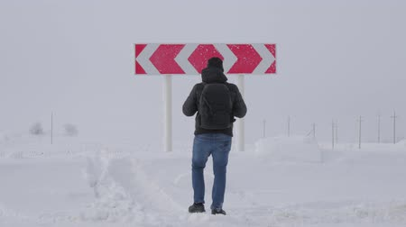 kryzys : Hiker man with backpack choose in a road fork between two different path directions at the winter on road. Concept of choose the correct way. Wideo