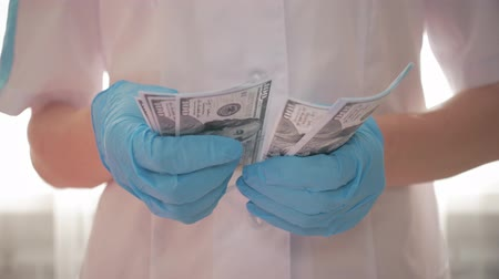 łapówka : Doctor in uniform and blue gloves recounts money, the concept of giving take for medical services. Corrupted medical doctor counting money. Doctor accepting bribe and counting dollar bills close-up.