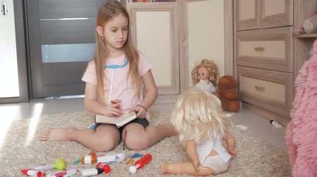 lalka : Beautiful little girl playing doctors with doll at home.