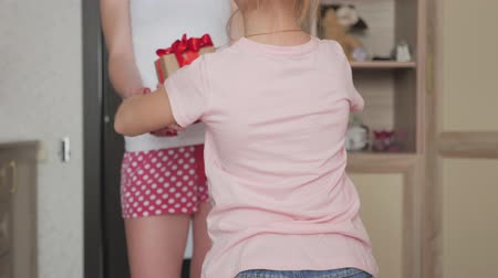 dávat : Charming little girl is giving her beautiful young mom a present at home. People, holidays and family concept - daughter kissing happy mother and giving her birthday present. Dostupné videozáznamy