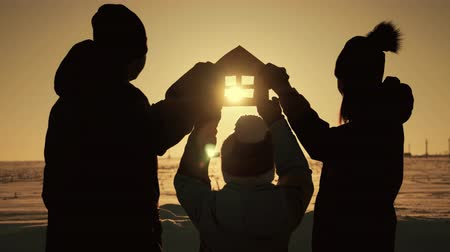 ailelerin : The family holds a paper house at sunset, dreaming of their own home. Silhouette of a paper house in hands at sunset in the sun. Stok Video