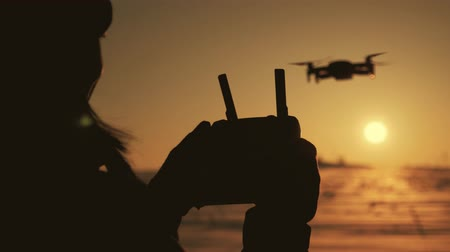 манипуляция : Girl operating a drone with remote control. Silhouette woman drone pilotage at sunset.