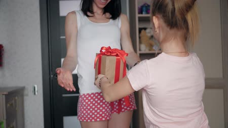 dát : Charming little girl is giving her beautiful young mom a present at home. People, holidays and family concept - daughter kissing happy mother and giving her birthday present. Dostupné videozáznamy