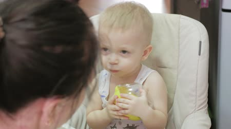 zabkása : Mother feeding her baby son with spoon. Mother giving healthy food to her adorable child at home. Happy baby boy with brown eyes eating porridge. Concept baby food. Stock mozgókép