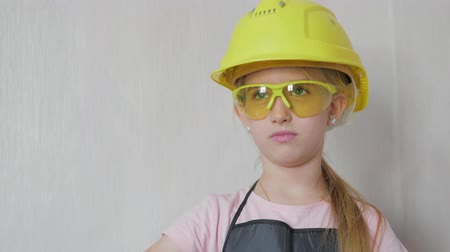 vállalkozó : Little girl in protective helmet and goggles, thinks about the project. Childhood, construction, architecture, building and people concept. Stock mozgókép