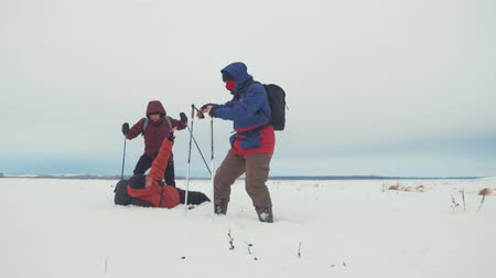 geada : Three tourist hikers with trekking poles, a backpack and snowshoes. Happy hikers group walking through in winter trip. Extreme sport, recreation. Teamwork concept. Stock Footage