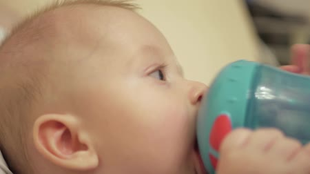 bottle feeding : Sweet baby boy sucking water in bottle at home. Stock Footage