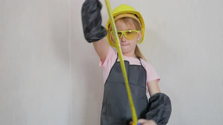adorable : Little girl in protective helmet and goggles, thinks about the project. Childhood, construction, architecture, building and people concept. Stock Footage