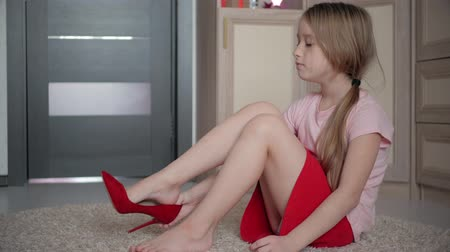 pięta : Little girl on the floor at home trying moms red high heel shoes. Wideo