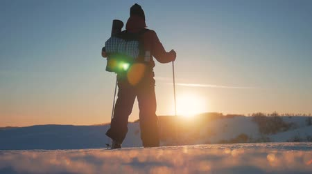 dağcı : A man with backpack and trekking sticks against the backdrop of winter mountains, beautiful sunset, snow on hills. A climber with trekking sticks walks through the snow. Concept winter hiking.