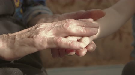 rebuliço : Hands of child and hands of an older woman. A child is hugging grandmothers hands.