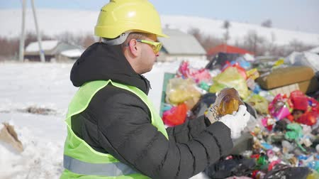 salva vidas : A engineer looks at a plastic bottle on the background of trash. The concept of environmental problems plastic garbage, illegal dumps. Vídeos
