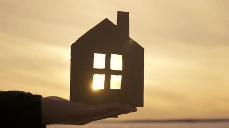 охрана : Silhouette hand with paper house at sunset background.