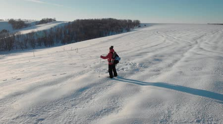 hátizsákkal : Aerial view young man hiking on top of snowy mountain at beautiful winter sunset. Male mountaineer with trekking poles and a backpack walking on extreme winter expedition tour. Stock mozgókép