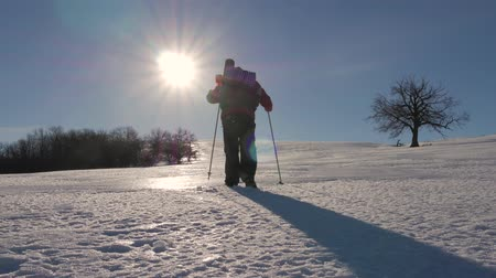 caminhadas : A man with backpack and trekking sticks against the backdrop of winter mountains, beautiful sunset, snow on hills. A climber with trekking sticks walks through the snow. Concept winter hiking.
