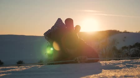 dağcı : Mountaineer reaches the top of a snowy mountain. A climber with backpack climbs up a snowy slope. Sunset sky on a horizon. Hiker in a winter adventure. Stok Video