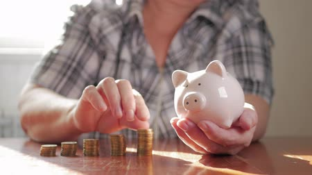 efektivní : Woman putting coin in piggy bank, saving money concept. Future needs loan education or mortgage credit spend vacation of dream effective buying financial risk.