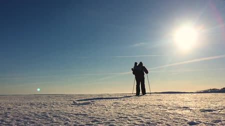 raquettes à neige : Silhouette of man with a backpack walking in a winter landscape on snowshoes. Trekking with hiking poles, blue sky and bright sun. Concept adventure activity hobby extreme. Vidéos Libres De Droits