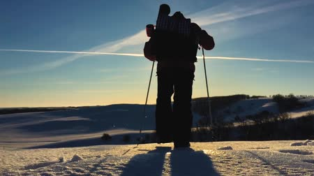 soğuk : Silhouette of man with a backpack walking in a winter landscape on snowshoes. Trekking with hiking poles, blue sky and bright sun. Concept adventure activity hobby extreme. Stok Video