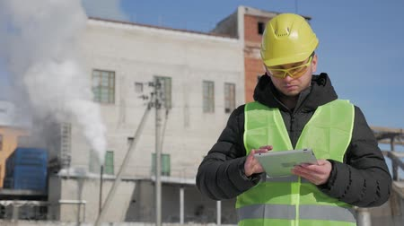 munkás : Engineer in hard hat is using a tablet computer in a industry factory.