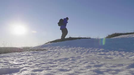 альпинист : Backpacker walking on snow mountain in winter. Man with backpack trekking in mountains. Winter hiking. Стоковые видеозаписи