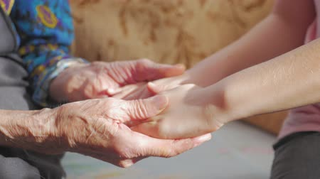 гладильный : Hands of child and hands of an older woman. A child is hugging grandmothers hands.