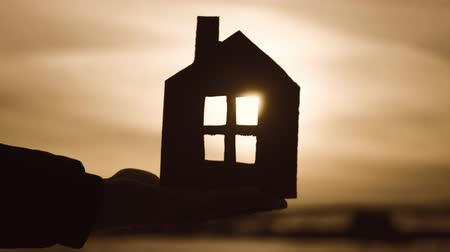 domy : Silhouette hand with paper house at sunset background.
