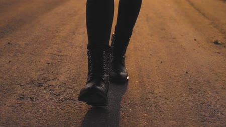 életmód : Young woman legs in black leather boots walking. Close up of girl shoes walking.