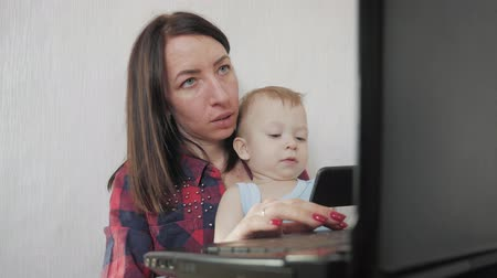 freelance work : Multi-tasking, freelance and motherhood concept - working mother baby boy and laptop computer at home. Family, mother working with child. Stock Footage