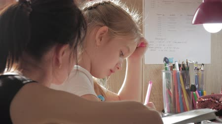 alfabetização : Young mother helps her daughter with her homework at on the table under the light of a lamp.