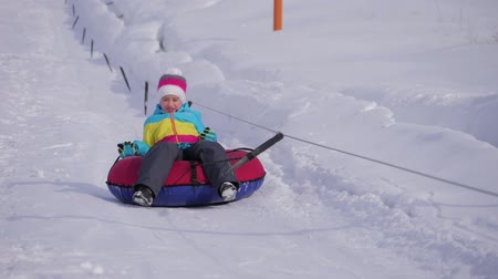 lesiklás : Young girl riding on inflatable snow tube from a hill.