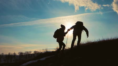 cliff : Couple hiking help each other silhouette in mountains. Teamwork couple hiking, help each other, trust assistance, sunset. Man giving hand a woman to help her to climb the mountain. Stock Footage