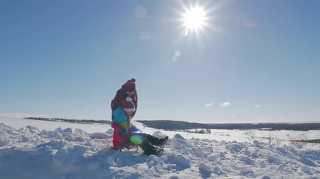 そり : Happy family mother and child daughter on a winter walk outdoors sledging. Beautiful family of mother and kids enjoying sunny winter day outdoors having fun sledging, lifestyle. 動画素材