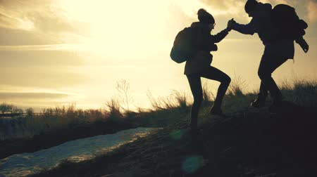 each other : Couple hiking help each other silhouette in mountains. Teamwork couple hiking, help each other, trust assistance, sunset. Man giving hand a woman to help her to climb the mountain. Stock Footage