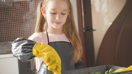 adorable : Fun little gardener care for plants. Cute little child girl planting seedlings. Spring concept, nature and care.