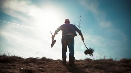 çiftçi : A man gardener with a shovel of the earth and the roots of the fruit tree, planting time on the garden plot. Spring garden work concept.