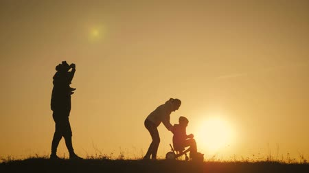 outside : Silhouettes family is together at sunset. Young boy learning to ride bicycle, father teach his son to ride a bike in the sunset.