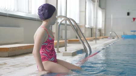čepice : Girl child in swimming pool. Smiling child leads a healthy lifestyle and keen on sports.