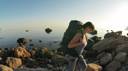 aktywność : The girl tourist with backpack is traveling in the mountains