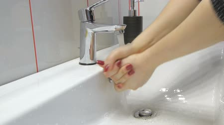 kezek : Woman washing her hands in bathroom