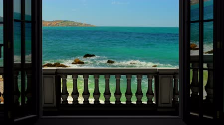 outside view : Looking out the window to the balcony and the sea Stock Footage