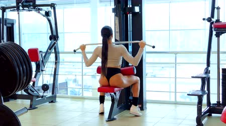 atleta : Athlete woman trains muscles of the back in the gym