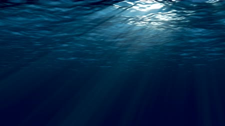 göl : Dark blue sea surface seen from underwater. Abstract waves underwater and rays of sunlight.