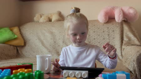 совершенство : Little blonde plays on the tablet and eats. Стоковые видеозаписи