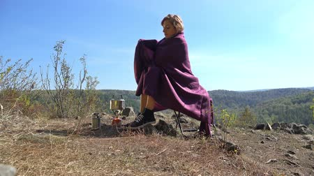 cobertor : Young blonde woman tourist wrapped in a vinous blanket sitting on camping chair in nature. Russia, Siberia, Salair