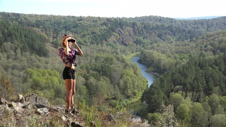 nações : Young blonde woman tourist   on a cliff looking through binoculars on the landscape with the river. Russia, Siberia, Salair