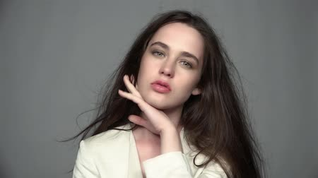 stílus : Slow motion video portrait of beauty young brunette resentful, woman portrait with green eyes and streaming hair in white fashion female jacket on gray background