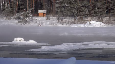 frazil ice : Bathhouse on the bank of winter Katun river with floating of ice in water, Altai, Siberia, Russia Stock Footage
