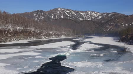 frazil ice : Aerial view on Altai river Katun near Elekmonar settlements with  floating of ice in water and mountains on background in winter season with zoom effect, Siberia, Russia